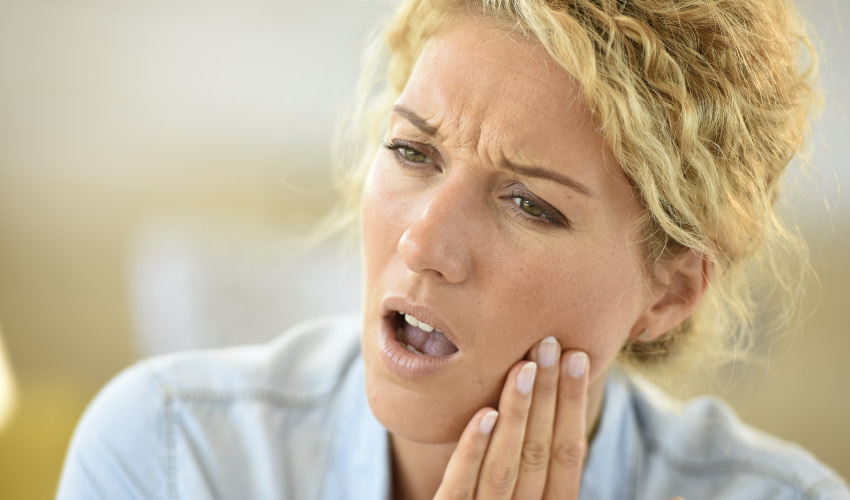 Blonde woman in a blue shirt cringes in pain as she touches her cheek due to extreme tooth pain