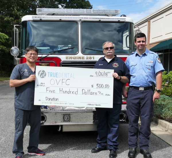 Dr. Shin with the Odenton Volunteer Fire Company holding a $500 check donation in front of a fire truck