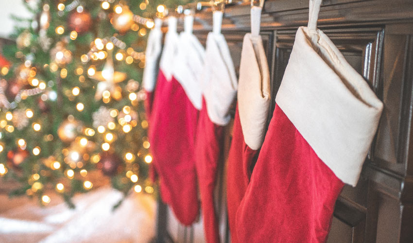 Closeup of red holiday stockings hanging on a brown mantle near a Christmas tree