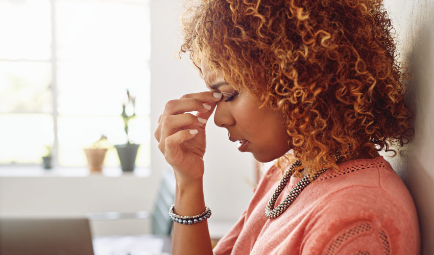 Curly-haired woman pinches the bridge of her nose in pain due to a headache from sleep apnea