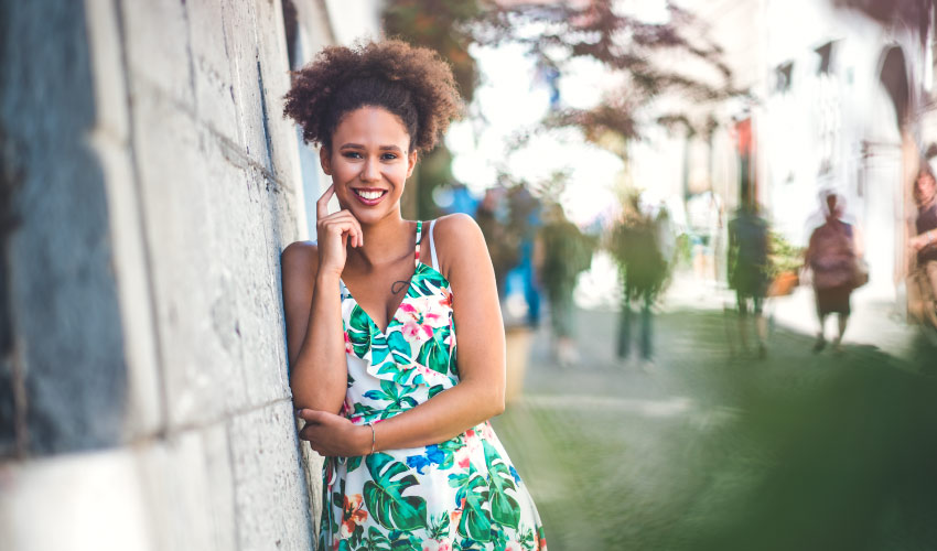 Curly-haired woman wearing a floral summer dress against a cement wall