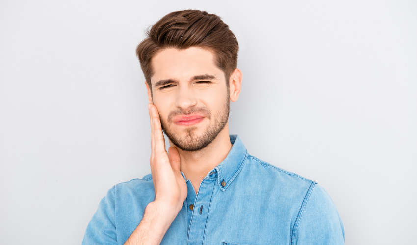 brunette man wearing a denim shirt cringes in pain and touches his cheek due to a toothache