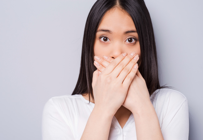 Brunette woman with bleeding gums covers her mouth with her hands in embarrassment