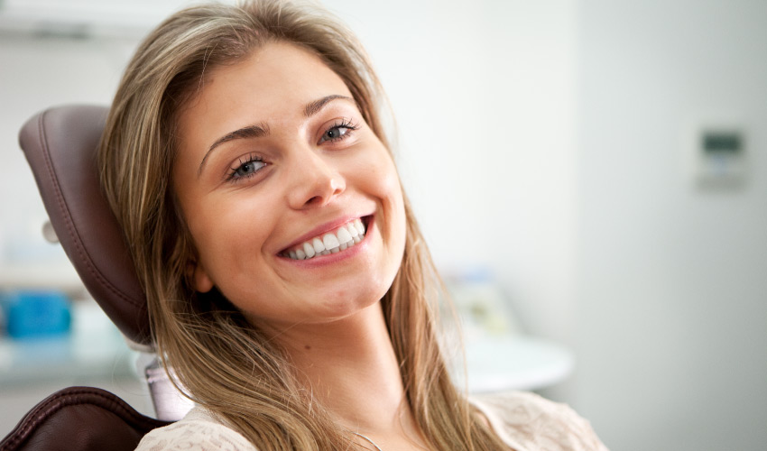 Brunette woman in a dental chair smiles after receiving an oral cancer screening at True Dental in Odenton, MD