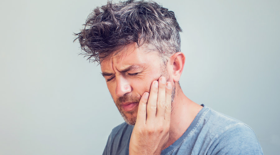 Middle-aged man cringes and touches his jaw due to jaw pain after waking up