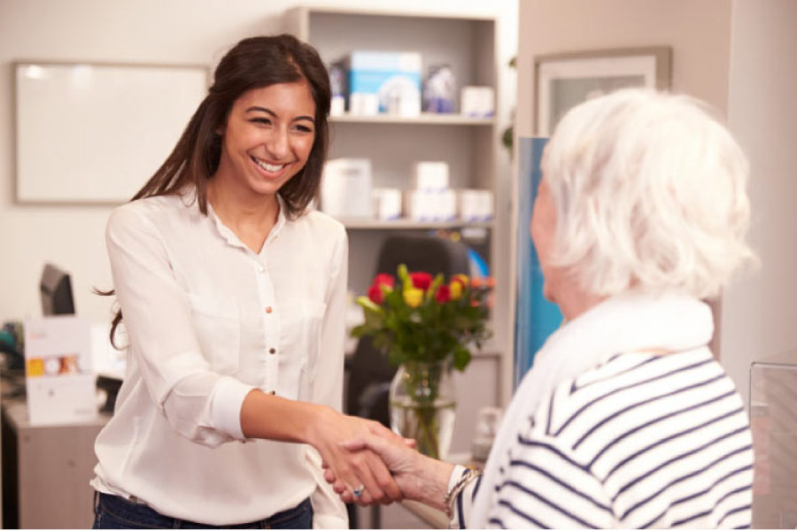 receptionist warmly greets a senior patient at the family dentist office